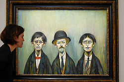 "© Licensed to London News Pictures. 17/07/2019. LONDON, UK. A staff member views ""Father and Two Sons"", 1950, by L.S. Lowry at the preview of ""Brave New Visions: The Émigrés who transformed the British Art World"", a new exhibition at Sotheby's gallery in New Bond Street which runs 17 July to 9 August 2019.  The show is also part of ""Insiders / Outsiders"", a nationwide, year long festival celebrating refugees from Nazi Europe and their contribution to British culture.  Photo credit: Stephen Chung/LNP"