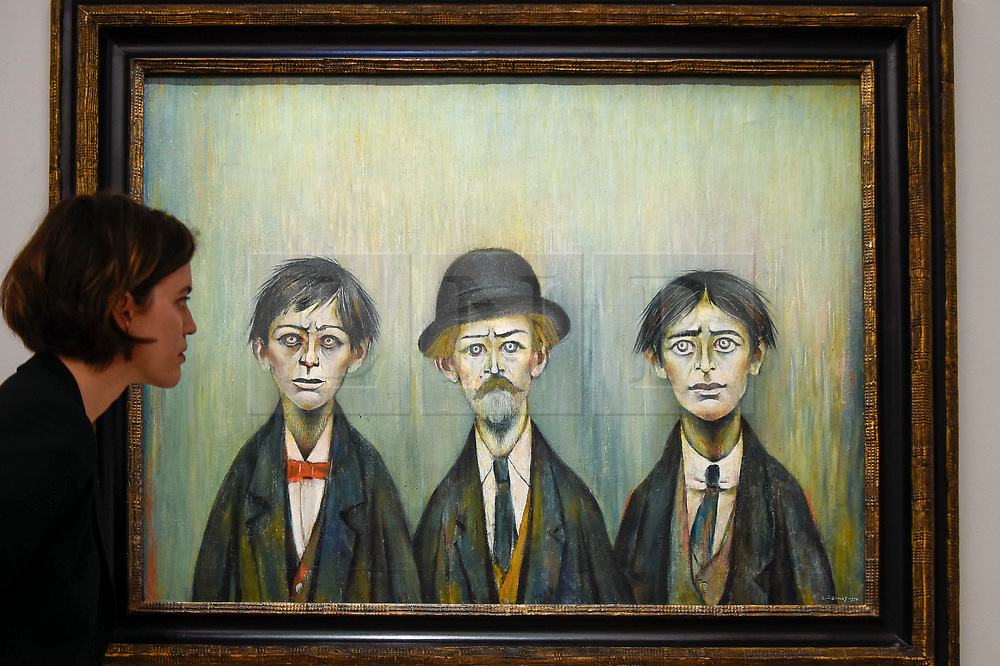 """© Licensed to London News Pictures. 17/07/2019. LONDON, UK. A staff member views """"Father and Two Sons"""", 1950, by L.S. Lowry at the preview of """"Brave New Visions: The Émigrés who transformed the British Art World"""", a new exhibition at Sotheby's gallery in New Bond Street which runs 17 July to 9 August 2019.  The show is also part of """"Insiders / Outsiders"""", a nationwide, year long festival celebrating refugees from Nazi Europe and their contribution to British culture.  Photo credit: Stephen Chung/LNP"""