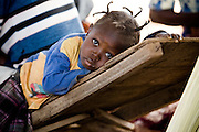 Girl lying on a wooden chair. Northern Ghana, Thursday November 13, 2008.