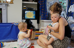 Mother and twin babies watching Tellytubbies on tv, UK