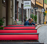 Stockholm, Sweden -- July 16, 2019. A Swedish businessman studies his mobile phone whil sitting in an outdoor cafe.