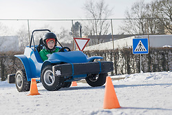 Boy driving electric toy car on snow covered road