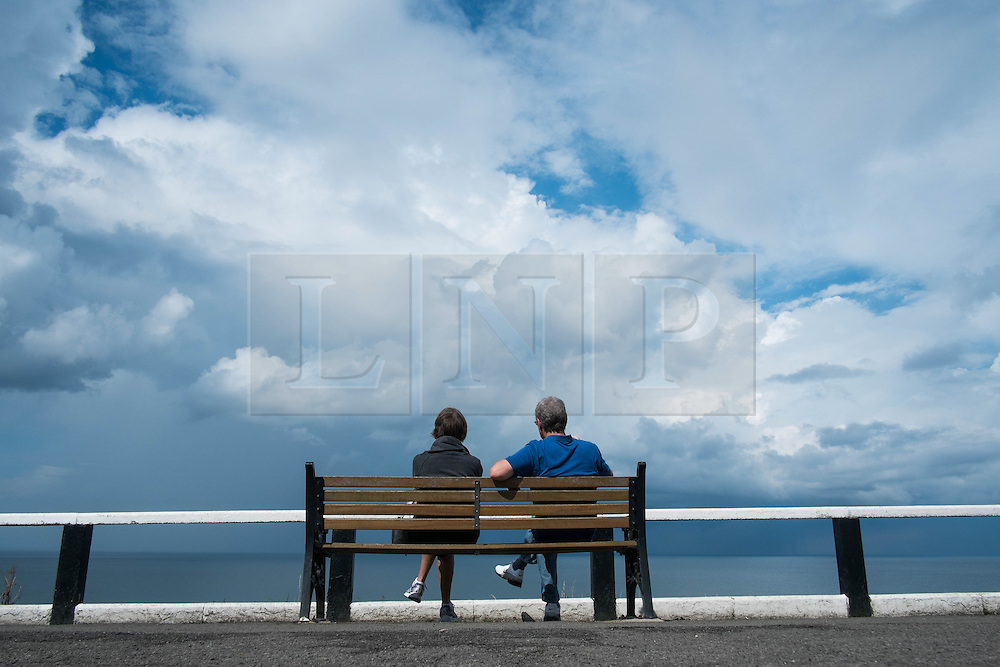 © Licensed to London News Pictures. <br /> 06/08/2014. <br /> <br /> Saltburn by the Sea, United Kingdom<br /> <br /> A couple sit and look out to sea from the upper promenade in Saltburn by the Sea in Cleveland as storm clouds build.<br /> <br /> Photo credit : Ian Forsyth/LNP