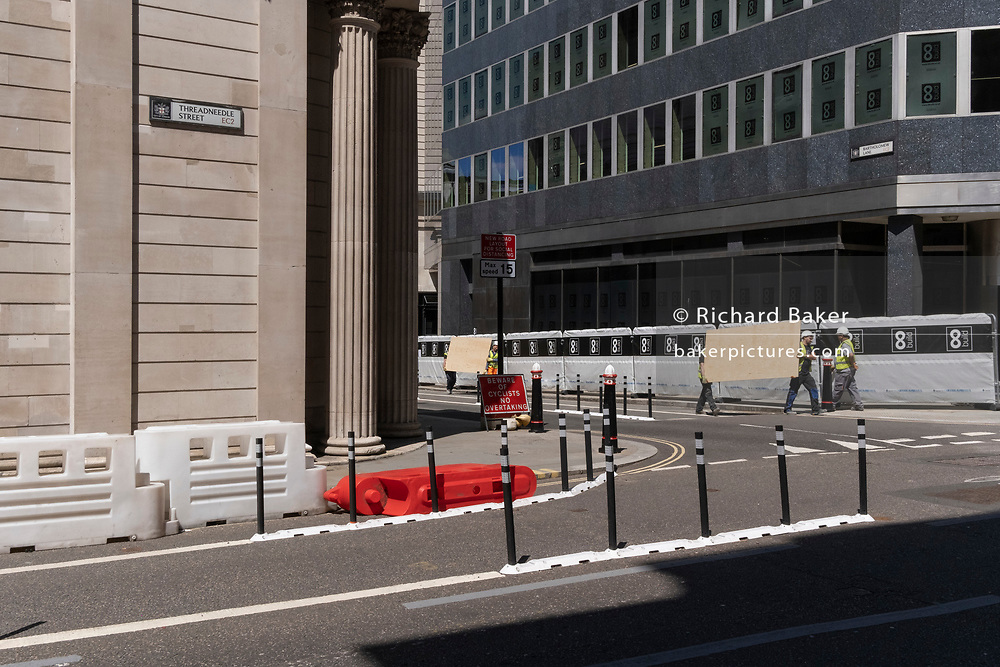 Construction workmen carry new plyboards into a nearby site alongside the Bank of Ebngland on Threadneedle Street in the City of London, the capital's financial district, on 8th June 2021, in London, England.