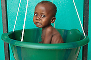 Garsiline Koko, 3, who suffers from malnutrition, is being weighed at the Pipeline health center in Monrovia, Montserrado county, Liberia on Monday April 2, 2012.