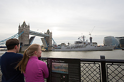 """© Licensed to London News Pictures. 29/11/2013. London, UK. People watch as the Belgian Frigate Louise Marie arrives in London on 29 November 2013 bringing """"sacred soil"""" from cemeteries of First World War Battlefields in Flanders and moors next to HMS Belfast on the River Thames. Tower Bridge was raised fully in complement, for the first time since the Diamond Jubilee Pageant in 2012. Photo credit : Vickie Flores/LNP"""