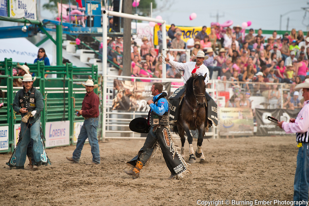 Steven Dent after his rid on Kesler Pro Rodeos bucking horse Mighty Fine as Jay Shaw and Travis Jordan move in to help in the Bareback event during the 3rd perf at the Northwest Montana Fair and  Rodeo Kalispell MT August 18th, 2018.  Photo by Josh Homer/Burning Ember Photography.  Photo credit must be given on all uses.