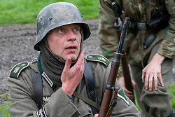A world war two Re-enactor portraying a German panzer grenadier from the Grossdeutschland Division. He is wearing the two Medal Ribbons, Iron Cross 2nd Class (top) and the Ost front or Eastern Front Medal nicknamed the Cold Meat Medal. Under the iconic German Stahlhelm he is wearing a Toque or tubular woven head scarf, standard issue to all German troops and carrying a mauser K98 rifle.<br /> Battle battle re-enactment on Pickering Showground during the 1940's Wartime Weekend