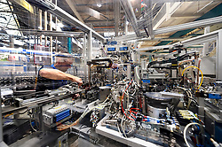 A Philips technician, services one of the robotic machines used to manufacture ceramic metal halide lamps, at the Philips Lighting factory, in Turnhout, Belgium, on Friday, Oct. 15, 2010. (Photo © Jock Fistick)