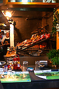 The gigantic huge charcoal grill with pieces of meat being cooked, view from the bar., in the restaurant El Palenque, the sword fish swordfish, in the Mercado del Puerto, the market in the port harbour harbor where many people go and eat and shop on weekends Montevideo, Uruguay, South America