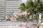 Waikiki beach is crowded with beach goers. The Sheraton Waikiki and the pink Royal Hawaiian Hotel are in the background.