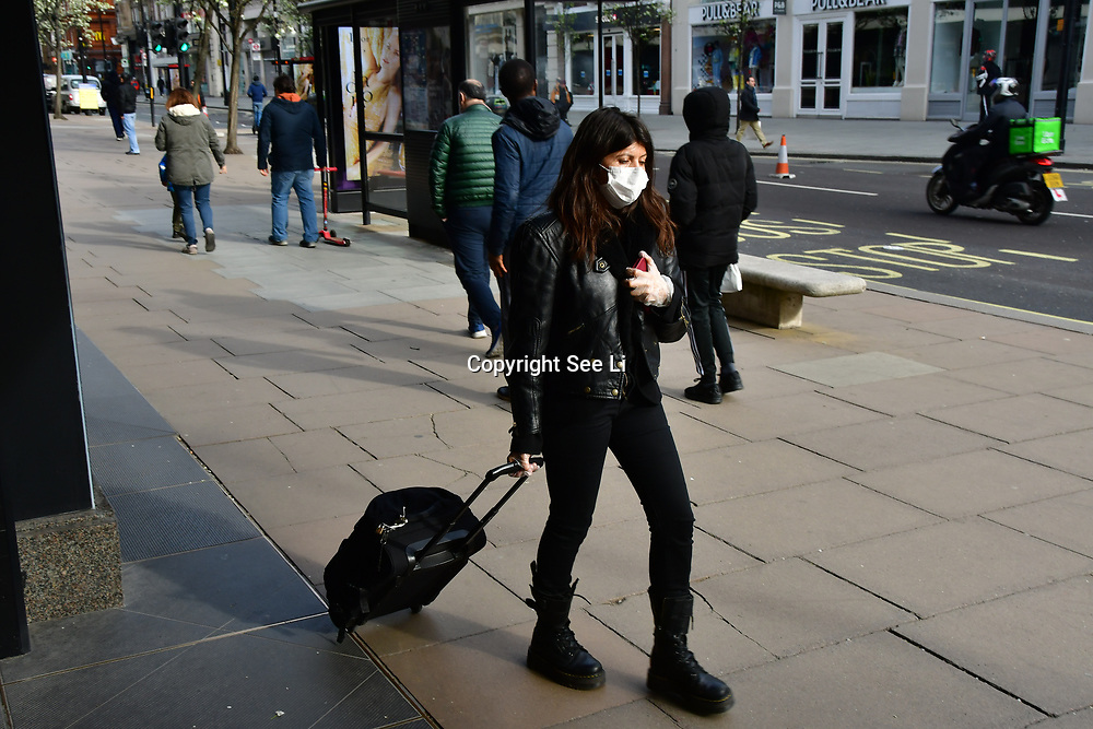 A woman wearing a mask at street during Coronavirus - Pandemic hit Oxford Street many shops closure a few open but empty on 21 March 2020, UK.