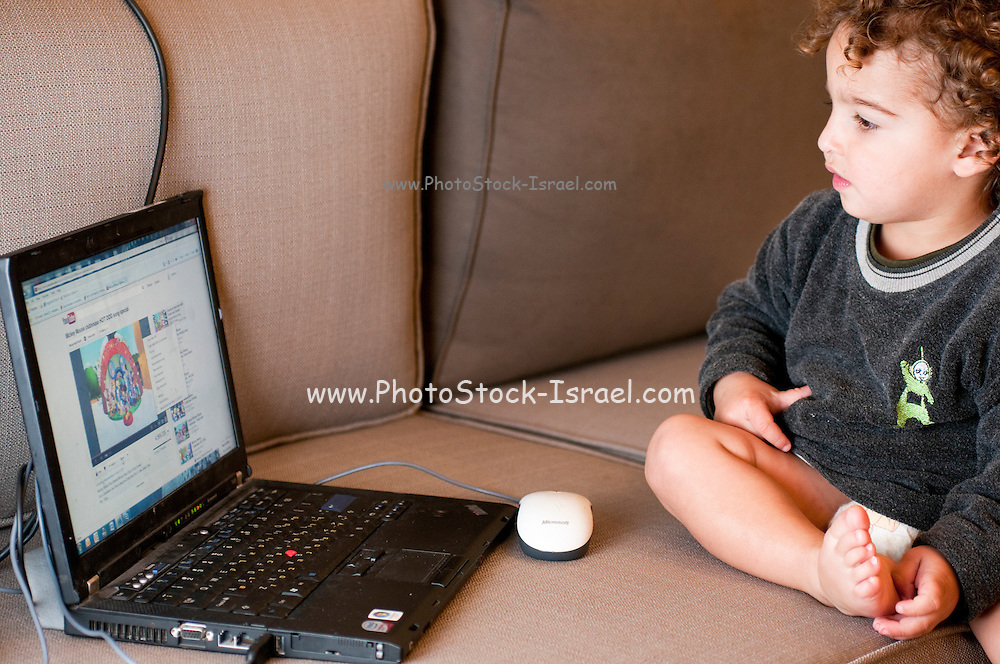 Toddler plays with a laptop computer