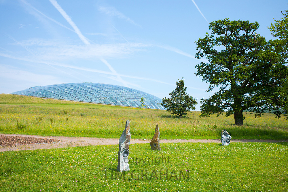 Dome shaped glass roof of The Great Glasshouse of the National Botanic Garden of Wales and stone sculptures.
