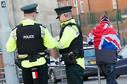 © Licensed to London News Pictures . 09/01/2013 . Belfast , UK . A man wrapped in a Union Jack flag and wearing a Union Jack hat alongside policemen outside the office of the Alliance Party on Newtownards Road , East Belfast , today (9th January 2013) . Regular protests have been taking place since the Belfast City Council voted to fly the Union Flag on designated days rather than every day . Photo credit : Joel Goodman/LNP