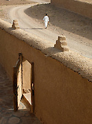 A man walks along a street in the village of Dadès in the Skoura Oasis, Morocco