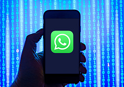 Person holding smart phone with  WhatsApp  logo displayed on the screen. EDITORIAL USE ONLY