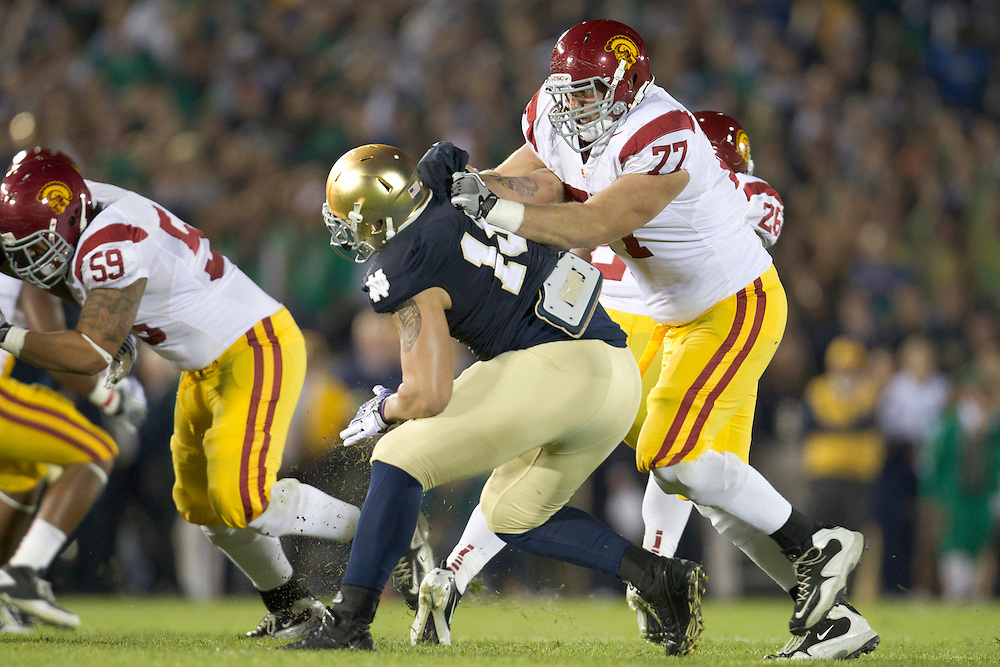 Notre Dame defensive end Aaron Lynch (#19) and USC offensive tackle Kevin Graf (#77) battle on the line of scrimmage during first quarter action of NCAA football game between Notre Dame and USC.  The USC Trojans defeated the Notre Dame Fighting Irish 31-17 in game at Notre Dame Stadium in South Bend, Indiana.