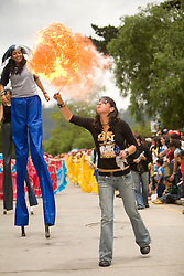 South America, Ecuador, Cuenca.  Stilt-walker and fire-blower in annual parade and festival to celebrate founding of Cuenca in 1557.  Cuenca is a UNESCO World Heritage Site.