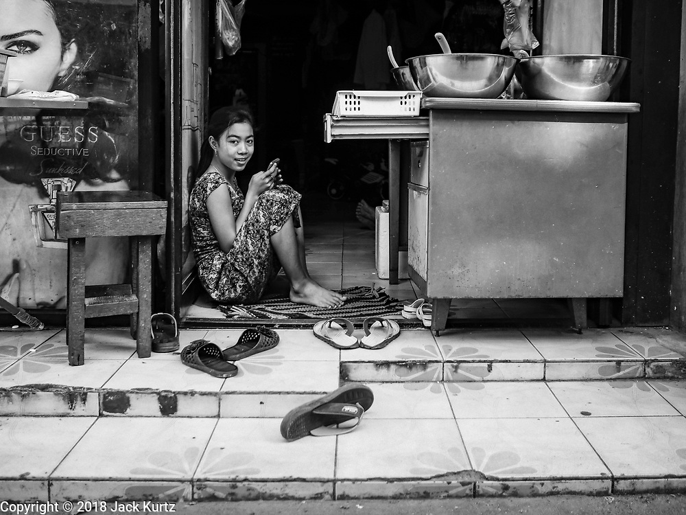 17 DECEMBER 2018 - BANGKOK, THAILAND: A girl plays on her smart phone in front of her home in a working class neighborhood behind Siam Paragon, an exclusive mall in central Bangkok. According to Credit Suisse Global Wealth Databook 2018, which surveyed 40 countries, Thailand has the highest rate of income inequality in the world. In 2016, Thailand was third, behind Russia and India. In 2016, the 1% richest Thais (about 500,000 people) owned 58.0% of the Thailand's wealth. In 2018, they controlled 66.9%. In Russia, those numbers went from 78% in 2016, down to 57.1% in 2018. The Thai government disagreed with the report and said the report didn't take government anti-poverty programs into account and that Thailand was held to an unfair standard because most of the other countries in the report are developed countries in the Organisation for Economic Co-operation and Development.    PHOTO BY JACK KURTZ