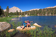Kids (ages 5 & 9) relaxing on the shore of Muir Lake, John Muir Wilderness, Inyo National Forest, Sierra Nevada Mountains, California