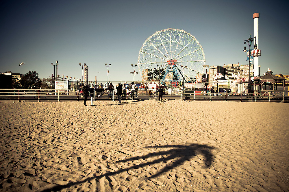 A palm tree shadow on Coney Island's beach with the boardwalk and the big wheel of the amusement park in the background, Brooklyn, New York, 2010.