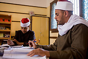 A schoolboy reads verses from the Koran in front of his religious teacher in a classroom at the Islamic Koom al-Bourit Institute for Boys in the village of Qum (Koom), on the West Bank of Luxor, Nile Valley, Egypt. Islam in Egypt is the dominant religion in a country with around 80 million Muslims, comprising 94.7% of the population, as of 2010. Almost the entirety of Egypt's Muslims are Sunnis, with a small minority of Shia and Ahmadi Muslims. The latter, however, are not recognised by Egypt.