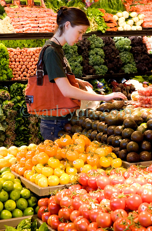 01 Feb 2006. Uptown, New Orleans, Louisiana.  Post Katrina. <br /> The Whole Foods supermarket reopens amidst great celebration 5 months after  the city was hit by Hurricane Katrina. A customer selects fruit and vegetables from the produce dept.<br /> Photo; Charlie Varley/varleypix.com