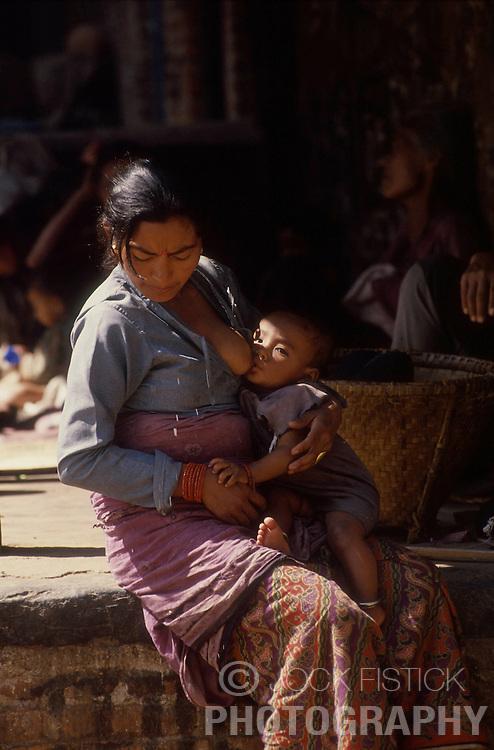 KATHMANDU, NEPAL - OCTOBER 1992 - A woman nurses her baby boy at a market in Kathmandu. (PHOTO © JOCK FISTICK)