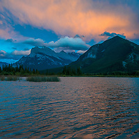 A sunset lights clouds over Mount Rundle, Sulphur Mountain (R) and Vermillion Lakes in Banff National Park, Alberta, Canada.