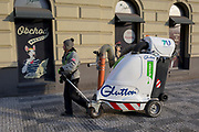 A city street cleaning operative pulls an electric Glutton waste vacuum cleaner past a dog shop on Milady Horakove street, Holesovice district, Prague 7, on 20th March, 2018, in Prague, the Czech Republic.