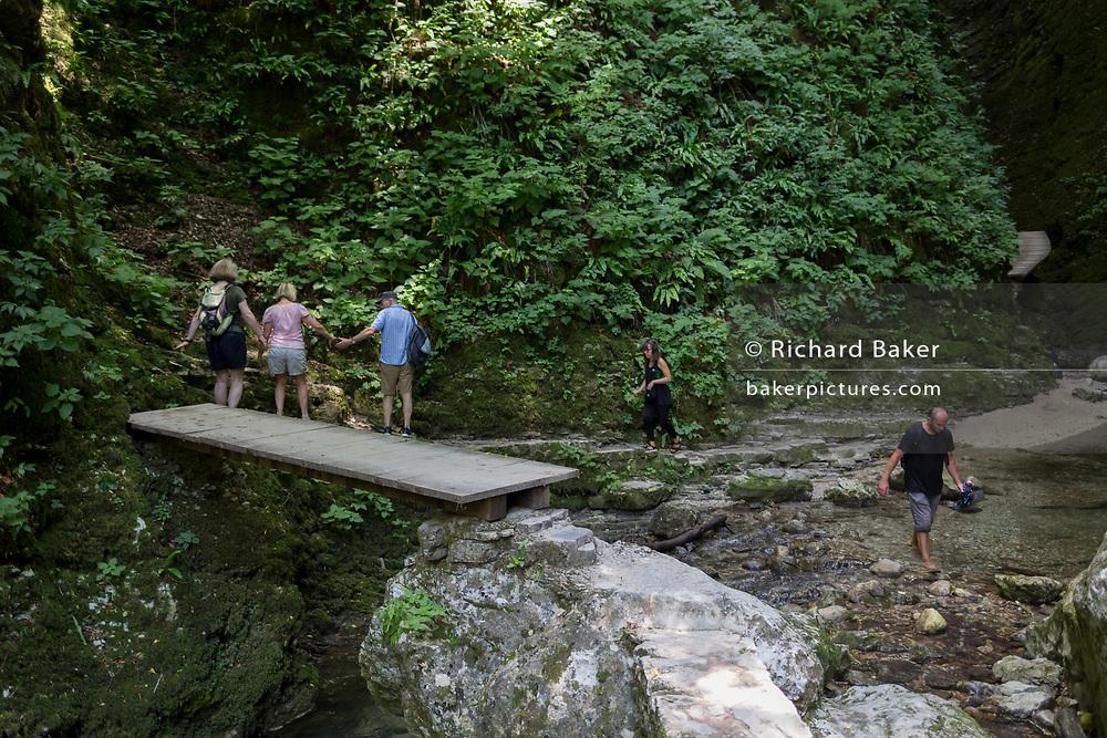 Adventurous walkers negotiate moderate terrain in the rocky gorge near the 15m high Kozjak Waterfalls, part of the Kobarid Heritage Trail, on 21st June 2018, in Kobarid, Slovenia.