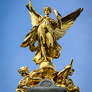 Gold Statue on Victoria Memorial Buckingham Palace London 169-110759708 The Victoria Memorial, dedicated to Queen Victoria, sits directly in front of Buckingham Palace, with Queen Victoria facing The Mall.