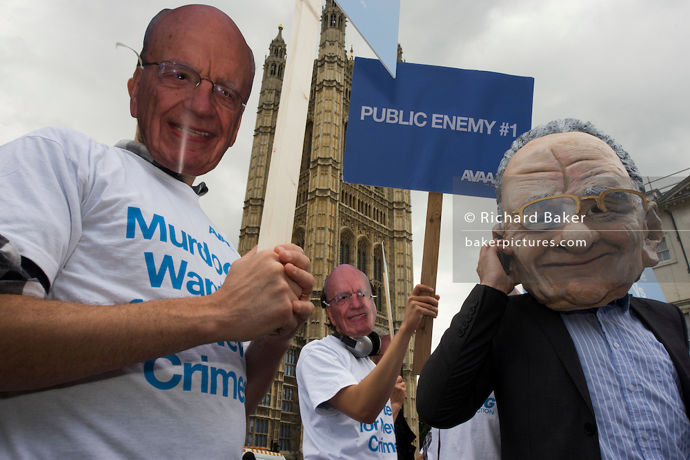 "Politcal action group Avaaz wear Rupert Murdoch masks outside Parliament during News International phone hacking scandals. Avaaz--meaning ""voice"" in several European, Middle Eastern and Asian languages--launched in 2007 with a simple democratic mission: organize citizens of all nations to close the gap between the world we have and the world most people everywhere want."