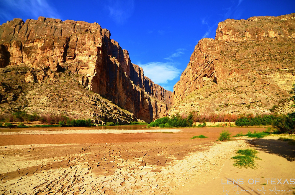 This was taken at Santa Elena Canyon on the US/Mexico border. The Rio Grande River runs through the canyon. In this photo, Texas is on the right side of the canyon and Mexico is on the left. The river is only 8-10 feet wide and only a few inches deep at this location. The water in the foreground is runoff in a usually dry creek bed from a thunderstorm the night before this shot was taken.
