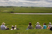 A group of country ramblers rest for lunch on the sea defence embankment of Halstow Marshes on the Kent Thames estuary marshes, potentially threatened by the future London airport.