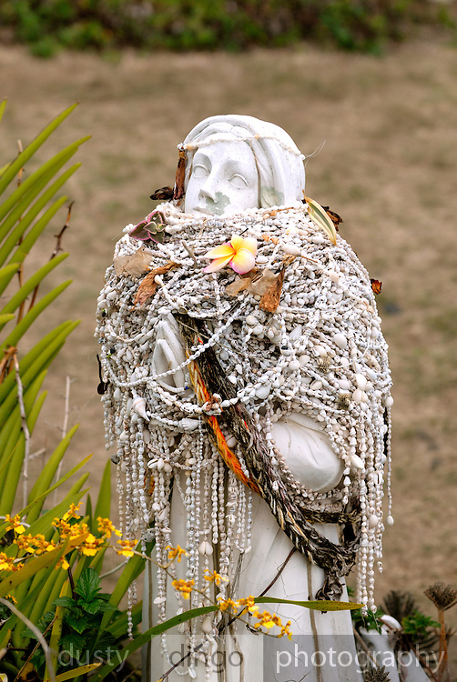 Statue bedecked with leis made of small shells, in the garden of St. Benedict's Roman Catholic Church, also known as the Painted Church. Honaunau, Kona, Big Island, Hawaii