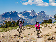 Ritter & Banner Peaks rise behind hikers doing yoga tree pose on Mammoth Crest. Inyo National Forest, Mammoth Lakes, California, USA. We hiked from Lake George Trailhead to Crystal Lake (side trip) and Mammoth Crest for 7 miles with 2000 ft gain.