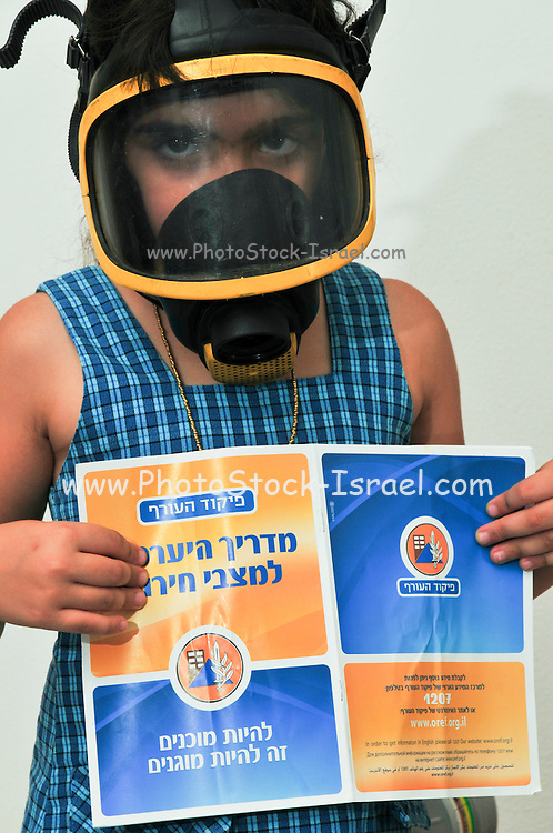 Gas Masks - All Israeli residents were issued gasmasks as a first means of defence against chemical or biological warfare. Young Girl of Seven tries on her gas mask looking at the user manual