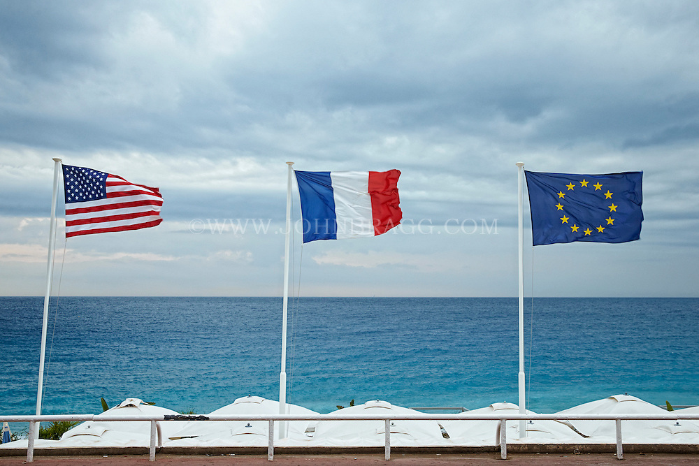 View of USA, French, and Europe Flags found along the Promenade des Anglais, Nice, France.