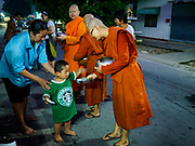 13 JANUARY 2019 - NAKHON PATHOM, THAILAND:  A boy gives food to female monks from Wat Songdhammakalyani on the monks' alms rounds. The Sangha Supreme Council, Thailand's governing body of Buddhist monks, bans the ordination of female monks, but hundreds of Thai women have gone abroad, mostly to Sri Lanka and India, to be ordained. There are about 270 women monks in Thailand and about 250,000 male monks. There are 7 monks and 6 novices at Wat Songdhammakalyani in Nakhon Pathom. It was the first temple in Thailand to have female monks. The temple opened 60 years ago and has always been a temple of women monks. Women can be ordained as novices in Thailand, but to be ordained as a full monk would require the participation of 10 female monks and 10 male monks, and male monks in Thailand are barred from participating in women's ordination ceremonies.    PHOTO BY JACK KURTZ
