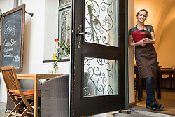 Portrait of woman with menu cards standing by open door at restaurant