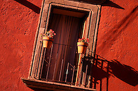 Shadows fall over red painted wall with balcony and geranium pots, San Miguel de Allende Mexico