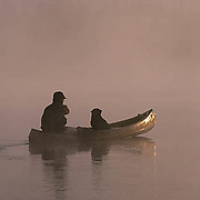 Canoeist and dog paddling across small northern lake.Early foggy, morning. Northern Minnesota.
