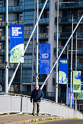 Glasgow, Scotland, UK. 21st October 2021. Final preparations underway at the site of the UN Climate Change Conference COP26 to be held in Glasgow from Oct 31st. Pic; Man walks below banners advertising COP26. Iain Masterton/Alamy Live News.