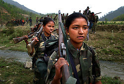 "RUKUM DISTRICT, NEPAL, APRIL 22, 2004:  Maoist insurgents celebrate in Rukum district April 22, 2004 weeks after their attack on government troops in Beni when they overran the district headquarters, looting a bank, destroying the jail and torching government office buildings. The government said that 32 security personnel died in the clash and 37 were kidnapped. The clash was one of the deadliest since 1996 when fighting began to topple the constitutional monarchy and install a communist republic. The guerrillas' strength is hard to gauge. Analysts and diplomats estimate there about 15,000-20,000 hard-core fighters, including many women, backed by 50,000 ""militia"".  In their remote strongholds, they collect taxes and have set up civil administrations, and ""people's courts"" to settle rows. They also raise money by taxing villagers and foreign trekkers. Though young, they are fearsome fighters and  specialise in night attacks and hit-and-run raids. They are tough in Nepal's rugged terrain, full of thick forests and deep ravines and the 150,000 government soldiers are not enough to combat this growing movement that models itself after the Shining Path of Peru. (Ami Vitale/Getty Images)"