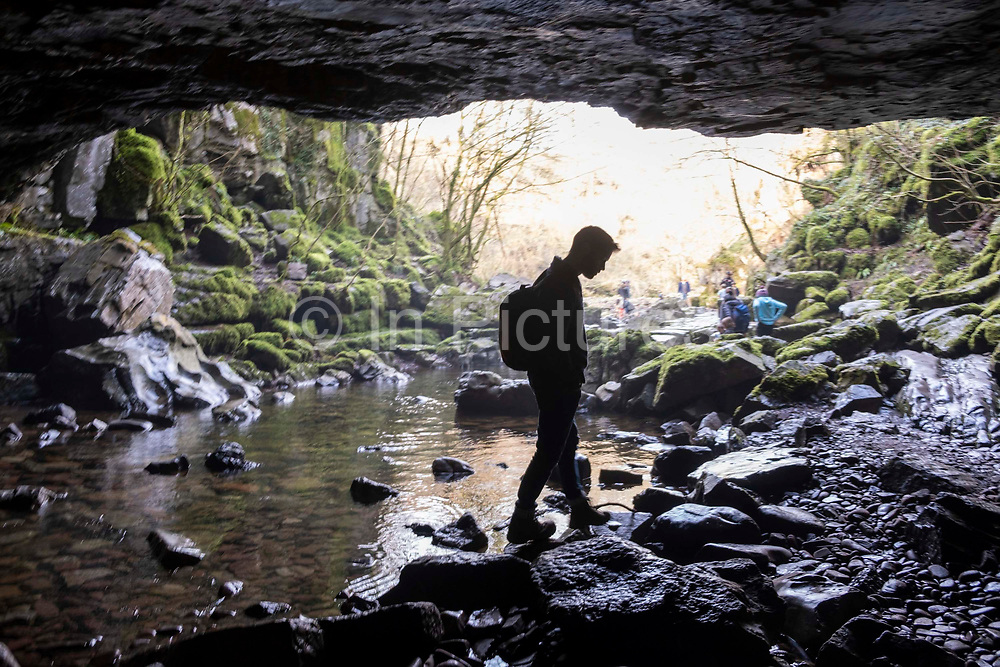 Silhouette of man waling across the river bed rocks at the entrance of Porth-yr-ogof Cave near the village of Ystradfellte, Brecon Beacons National Park, Wales, Powys, United Kingdom. The Afon Mellte River flows into the cave.