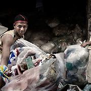 """Trabajadores """"Zabbaleen"""" almacenando diferentes tipos de plástico en el barrio de Mokattam . En medio del barrio de Manshiet Nasr a las afueras de El Cairo esta situado el asentamiento de Mokattam conocido como la """"Ciudad de la Basura"""" , está habitado por los Zabbaleen ,una comunidad de unos 45.000 cristianos coptos que viven desde hace varias décadas de reciclar los desperdicios que genera la capital egipcia: plástico, aluminio, papel y desechos órganicos que transforman en compost . La mayoría forman parte de la Asociación para la Protección del Ambiente (APE) una ONG que actúa en el área, cuyos objetivos son proteger el medio ambiente y aumentar el sustento de las recuperadores de basura de El Cairo. Según la ONU, el trabajo que se realiza en Mokattam como uno de los diez mejores ejemplos del mundo en el mejoramiento medioambiental. El Cairo , Egipto, Junio 2011. ( Foto : Jordi Camí )"""