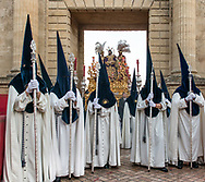 The float carrying Jesus Christ follow its brotherhood and is taken inside the walls of the old city of Cordoba on its way towards the Mezquita, the Cathedral originally built as a mosque. Andalusia, Spain.