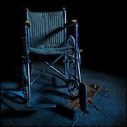 Wheelchair in blue light with a splintered floor